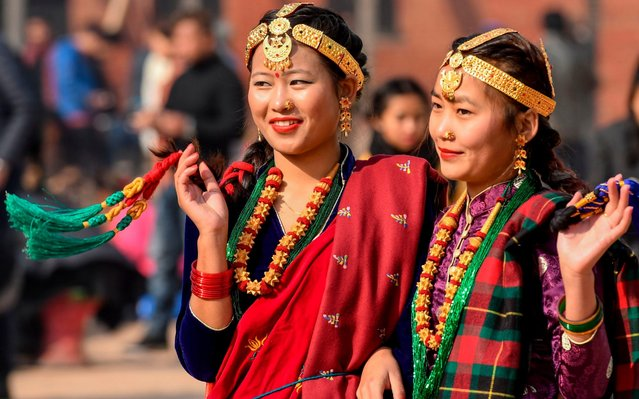"""Members of the indigenous Gurung community wearing traditional attire react as they take part in a New Year celebration ceremony known as """"Tamu Lhosar"""" in Kathmandu on December 31, 2019. (Photo by Prakash Mathema/AFP Photo)"""