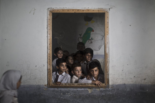 Pakistani schoolboys look out the window of their classroom at other classmates chanting prayers to commemorate the anniversary of Malala's shooting by Taliban, at a school in Rawalpindi, Pakistan, Wednesday, October 9, 2013. (Photo by Muhammed Muheisen/AP Photo)