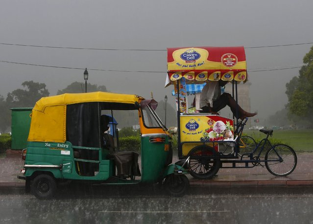 An ice-cream vendor takes shelter in his cart next to a parked auto-rickshaw during a heavy rain shower near India Gate in New Delhi, India, August 21, 2015. (Photo by Anindito Mukherjee/Reuters)