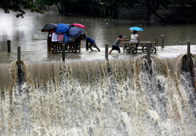 Filipinos riding on makeshift carts cross over an overflowing dam during a downpour in Las Pinas city, south of Manila, Philippines, 05 September 2017. According to the latest forecast from the Philippine Atmospheric Geophysical and Astronomical Services Administration (PAGASA) state weather bureau, typhoon signals were raised over Northern Luzon brought by a tropical storm (local name: Tropical Storm Kiko) and warned fisherfolks and small seacrafts not to venture onto the sea due to big waves. (Photo by Francis R. Malasig/EPA/EFE)