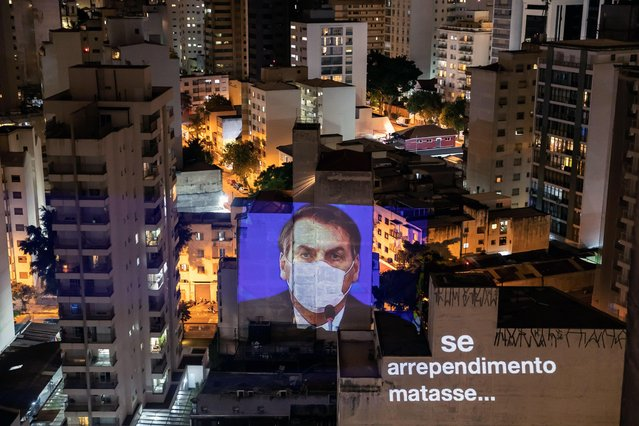 """President of Brazil Jair Bolsonaro's image is projected on to the facade of a building in Sao Paulo, Brazil, 19 March 2020. According to media reports, Bolsonaro initially called the coronavirus pandemic as a """"fantasy"""". (Photo by Sebastiao Moreira/EPA/EFE)"""