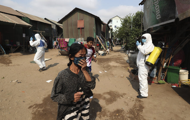 Villagers vacate the area as members of the non-profit Cambodian Children's Fund spray disinfectant to help curb the spread of the new coronavirus in the slum neighborhood of Stung Meanchey in southern Phnom Penh, Cambodia, on Tuesday, March 24, 2020. (Photo by Heng Sinith/AP Photo)
