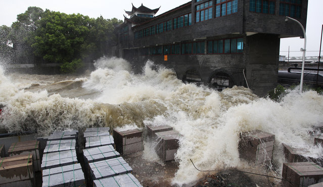 A tidal wave hits a bank along the Qiantang River on August 22, 2013 in Haining, China. The 12th typhoon Trami landed in Fujian province at 2:40 am and led gales and heavy rainfalls in east China. (Photo by ChinaFotoPress/ChinaFotoPress via Getty Images)
