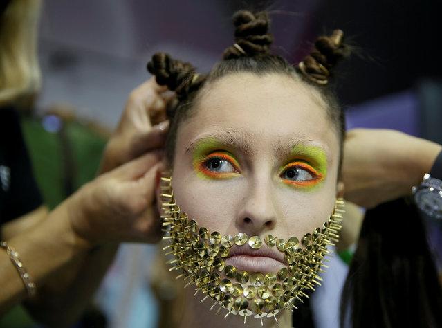 A model has her hair accessory put on  backstage at Ukrainian Fashion Week in Kiev, Ukraine, September 9, 2017. (Photo by Valentyn Ogirenko/Reuters)