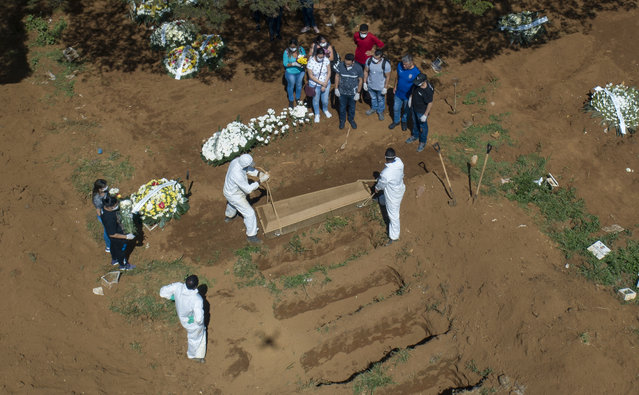 Cemetery workers bury a person at the Vila Formosa cemetery in Sao Paulo, Brazil, Wednesday, April 1, 2020. Vila Formosa cemetery, the largest in Latin America, has had a 30 percent increase in the number of burials after the start of the spread of the new coronavirus, according to the cemetery's administration. (Photo by Andre Penner/AP Photo)