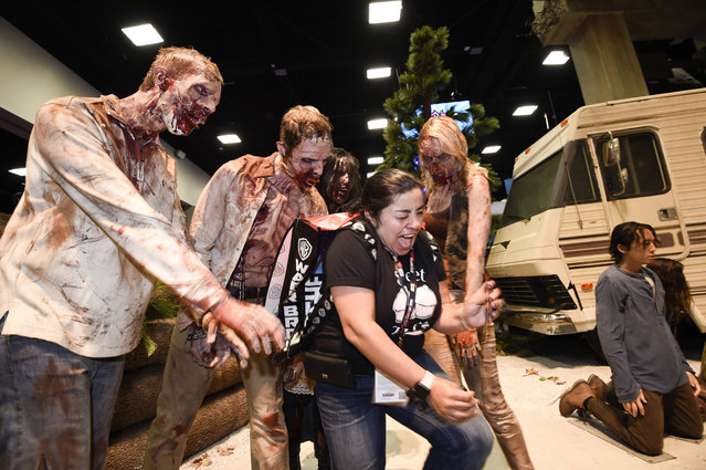 """Martha Guzman screams as she tries to pose for a photo with zombies at """"The Walking Dead"""" booth during Preview Night at Comic-Con International held at the San Diego Convention Center, Wednesday, July 20, 2016, in San Diego.  (Photo by [Denis Poroy/Invision/AP)"""