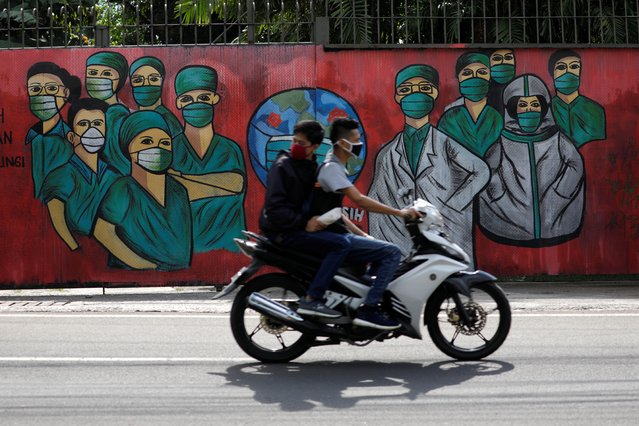 Men wearing face masks ride past a mural showing a thank you to country's medical workers tackling coronavirus disease (COVID-19) amid its spread, at a road in Depok, south of Jakarta, Indonesia, April 7, 2020. (Photo by Willy Kurniawan/Reuters)