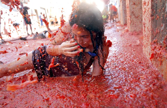 "A woman lays in a puddle of tomato juice during the annual ""Tomatina"" tomato fight fiesta in the village of Bunol, 50 kilometers outside Valencia, Spain, Wednesday, August 27, 2014. The streets of an eastern Spanish town are awash with red pulp as thousands of people pelt each other with tomatoes in the annual ""Tomatina"" battle that has become a major tourist attraction. (Photo by Alberto Saiz/AP Photo)"