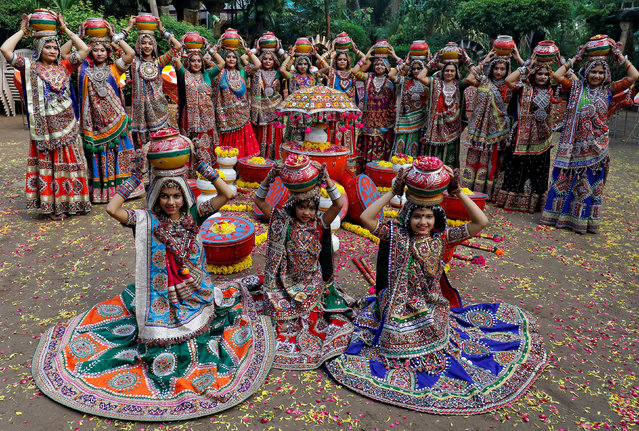 Performers dressed in traditional attire pose before performing Garba, a traditional folk dance, ahead of Navratri, a festival of nine days when devotees worship Hindu goddess Durga, in Ahmedabad, India, September 18, 2017. (Photo by Amit Dave/Reuters)