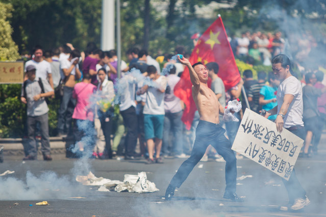 An anti-Japanese protester throws a gas canister during a demonstration on September 16, 2012 in Shenzhen, China. Protests have taken place across China in the dispute that is becoming increasingly worrying for regional stability. (Photo by Lam Yik Fei)