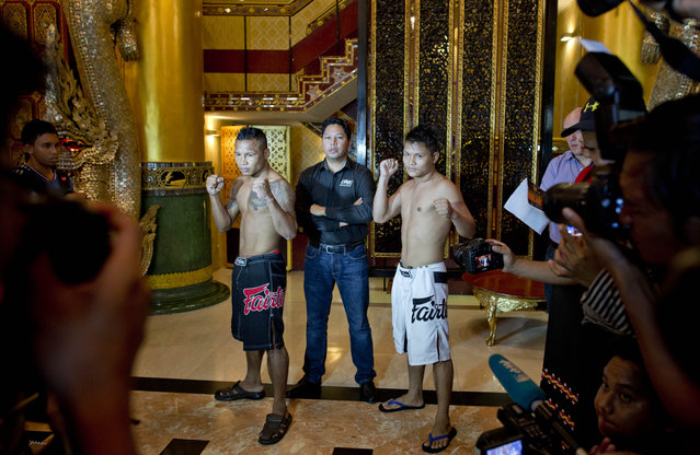 """In this Friday, July 17, 2015, photo, Hlit Hlit Lay, right, a member of the White New Blood lethwei fighters club, a Myanmar traditional martial-arts club which practices a rough form of kickboxing, poses with opponent Tha Pyay Nyo, left and """"One Championship"""" President Victor Cui, center, ahead of their featherweight fight at a mixed-martial-arts """"One Championship"""" event broadcast globally on cable television networks, in Yangon, Myanmar. (Photo by Gemunu Amarasinghe/AP Photo)"""