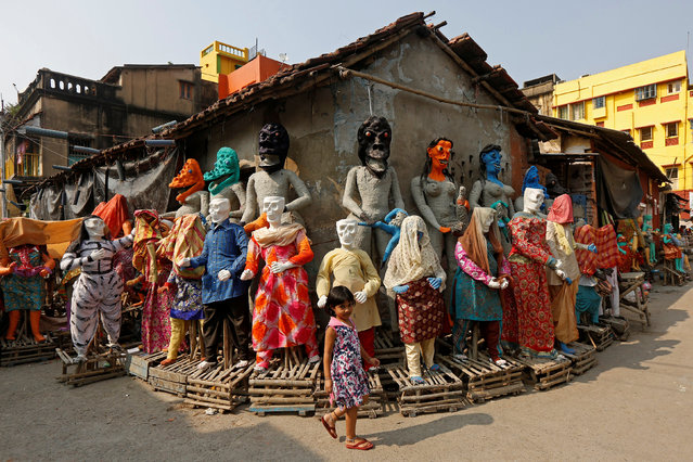 """A girl walks past clay idols of the Hindu mythological characters """"Dakinis"""" and """"Yoginis"""", who will be worshipped along with the Hindu goddess Kali during the Kali Puja festival, at a roadside workshop in Kolkata, October 17, 2017. (Photo by Rupak De Chowdhuri/Reuters)"""