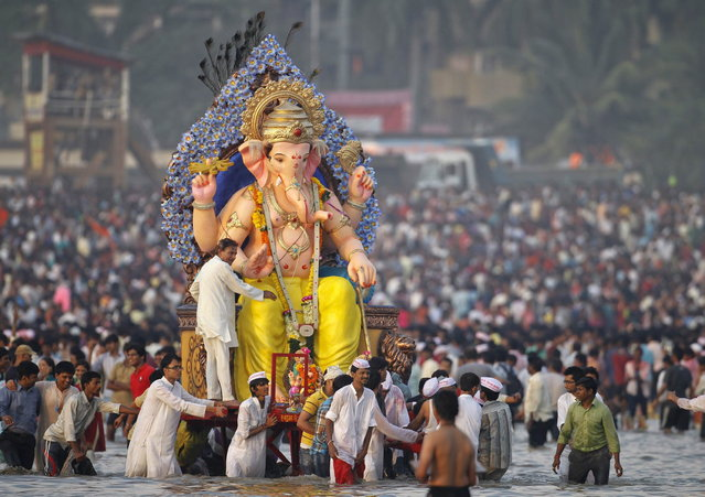 Devotees carry an idol of the Hindu elephant god Ganesh for immersion into the Arabian Sea on the last day of the Ganesh Chaturthi festival in Mumbai, September 29, 2012. Ganesh idols are taken through the streets in a procession accompanied by dancing and singing and later immersed in a river or the sea symbolising a ritual seeing-off of his journey towards his abode, taking away with him the misfortunes of all mankind. (Photo by Noah Seelam/AFP)