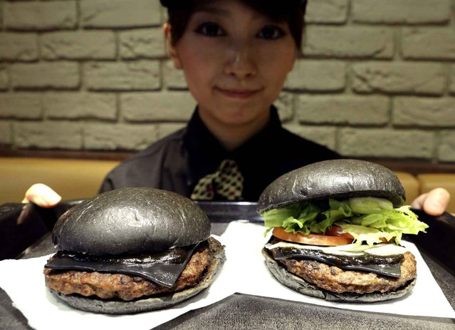 "Burger King employee Rumi Sekine shows the Kuro Diamond burger, right, and the Kuro Pearl burger at its Shibuya restaurant in Tokyo Tuesday, September 16, 2014. The international hamburger chain in Japan will launch the two new ""kuro burger"", or ""black burger"" menus that sport buns, cheese and sauce all in black color, starting on Friday, Sept. 19, for a limited period. The buns and cheese are darkened with bamboo charcoal while the beef patties made with black-pepper are topped with the garlic sauce using squid ink. (Photo by Koji Sasahara/AP Photo)"