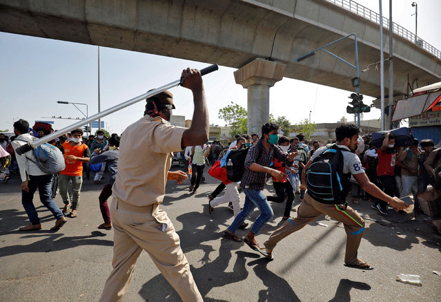 A policeman wields his baton to disperse migrant workers as they were demanding train service to their home state of Bihar, after a limited reopening of India's giant rail network following a nearly seven-week lockdown to slow the spreading of the coronavirus disease (COVID-19), in Ahmedabad, India, May 17, 2020. (Photo by Amit Dave/Reuters)