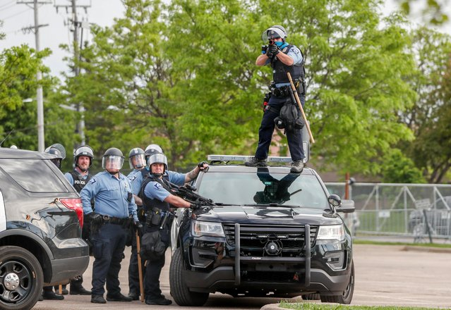 A police officer aims before firing at protesters gathered near the Minneapolis Police third precinct after a white police officer was caught on a bystander's video pressing his knee into the neck of African-American man George Floyd, who later died at a hospital, in Minneapolis, Minnesota, U.S. May 27, 2020. (Photo by Eric Miller/Reuters)