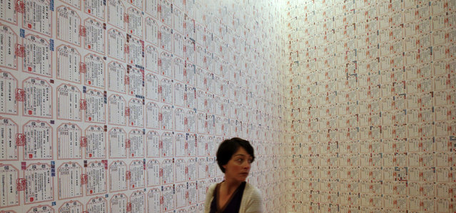 """A woman walks next to the installation """"IOU"""", made up of certificates of debt, by Chinese artist Ai Weiwei during a media preview of the exhibition """"Evidence"""" at the Martin-Gropius Bau in Berlin, April 2, 2014. (Photo by Fabrizio Bensch/Reuters)"""