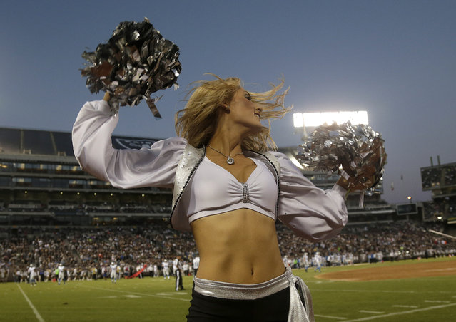 An Oakland Raiders cheerleader performs during an NFL preseason football game against the Detroit Lions in Oakland, Calif., Friday, August 15, 2014. (Photo by Marcio Jose Sanchez/AP Photo)