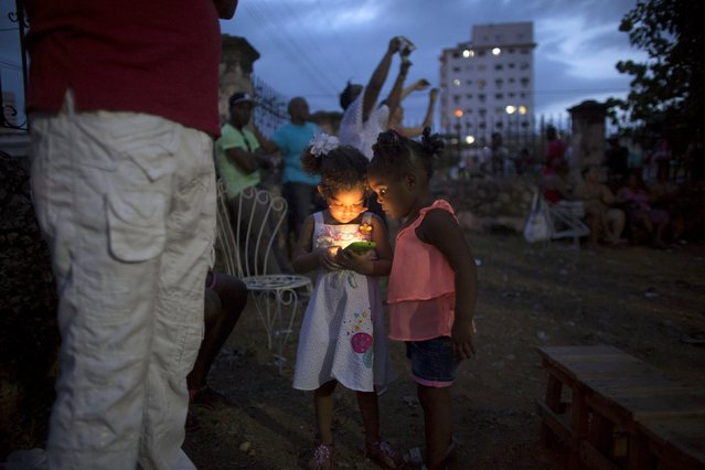 Jaimee Vilarino, 3, (L), plays with a mobile phone during a party for Yensy Villarreal, 9, (not pictured), in celebration for becoming a Santero after passing a year-long rite of passage in the Afro-Cuban religion Santeria, Havana, July 5, 2015. Santeria adherents can only hope the upcoming visit from Pope Francis will somehow nudge the Church toward recognizing the millions of Cubans who identify with both religious traditions. (Photo by Alexandre Meneghini/Reuters)