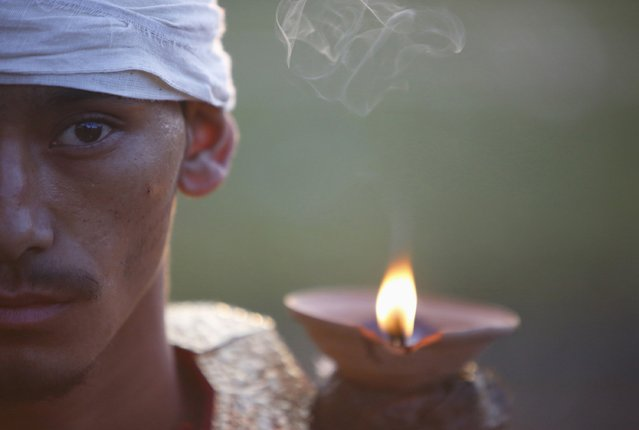 """A devotee sits with lighted oil lamps while offering prayers during the """"Dashain"""", Hinduism's biggest religious festival in Bhaktapur October 3, 2014. (Photo by Navesh Chitrakar/Reuters)"""