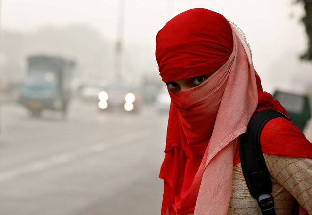 A woman wearing a scarf to cover her face looks on as she waits for a passenger bus on a smoggy morning in New Delhi, India, November 8, 2017. (Photo by Saumya Khandelwal/Reuters)