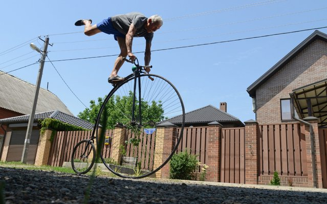 Bicycle and velomobile builder, multiple world champion in velomobile racing Sergei Dashevsky rides one of his bicycles by his house in Krasnodar, Russia on June 10, 2020. The bicycle built by Sergei Dashevsky measuring 8.4x16.5x16.1 centimeters is included in the Russian Book of Records as the smallest bicycle in Russia. (Photo by Igor Onuchin/TASS)