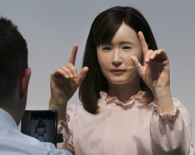 A prototype of Japanese electronics company Toshiba's female android Ms. Aiko Chihira performs sign language to a visitor during the annual CEATEC Japan advanced technologies show in Chiba Tuesday, October 7, 2014. The robot features its smooth gestures and expressions, giving a self-introduction to visitors. Exhibitors used such attention-grabbing gadgets to showcase their technology and stand out at the event that started Tuesday. (Photo by Koji Sasahara/AP Photo)