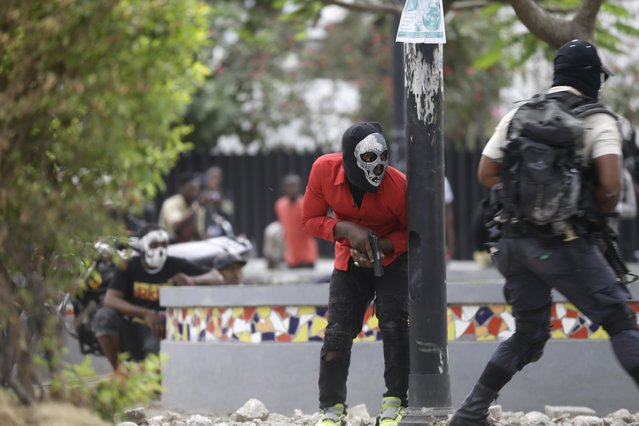 Armed off-duty police officers take cover during and exchange of gunfire with army soldiers during a protest over police pay and working conditions, in Port-au-Prince, Haiti, Sunday, February 23, 2020. (Photo by Dieu Nalio Chery/AP Photo)