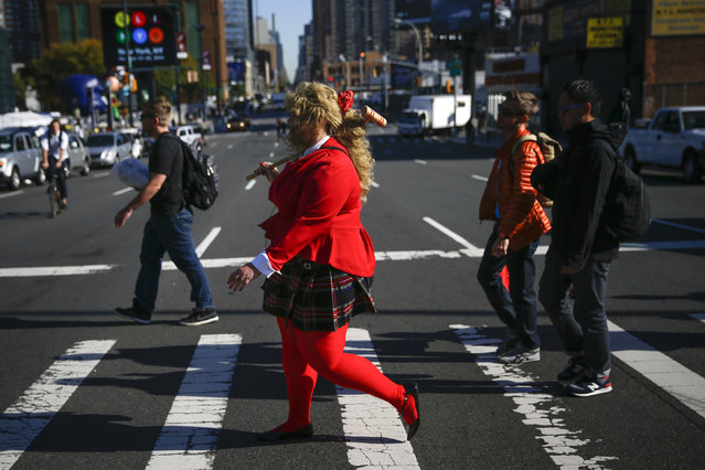 A woman crosses 10th avenue on way to the New York's Comic-Con convention October 9, 2014. The event draws thousands of costumed fans, panels of pop culture luminaries and features a sprawling floor of vendors in a space equivalent to more than three football fields in Javits Center. (Photo by Shannon Stapleton/Reuters)