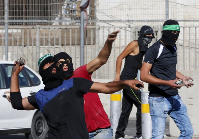 Palestinians hurl stones towards Israeli border police during clashes at a checkpoint between Shuafat refugee camp and Jerusalem September 18, 2015. (Photo by Ammar Awad/Reuters)