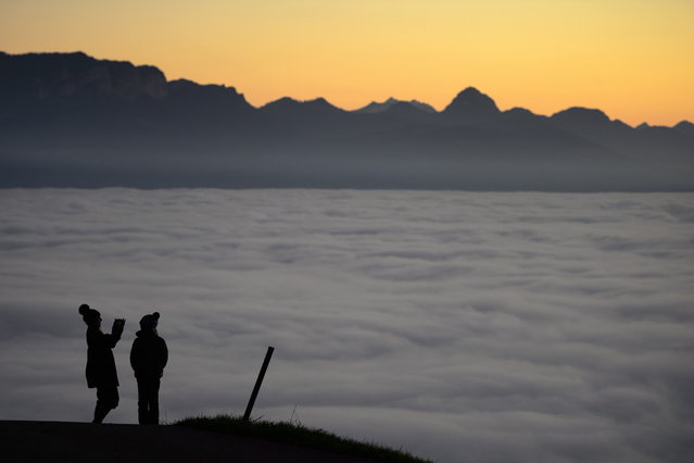 Two persons are seen in silhouette over heavy fog hanging above Lake Geneva (Lac Leman) on November 16, 2012 above Riex near Lausanne, western Switzerland. (Photo by Fabrice Coffrini/AFP Photo)