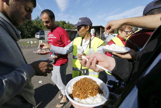 "Migrants receive meals from members of refugee aid organisations during the distribution of food at the makeshift camp called ""The New Jungle"" in Calais, France, September 20, 2015. (Photo by Regis Duvignau/Reuters)"