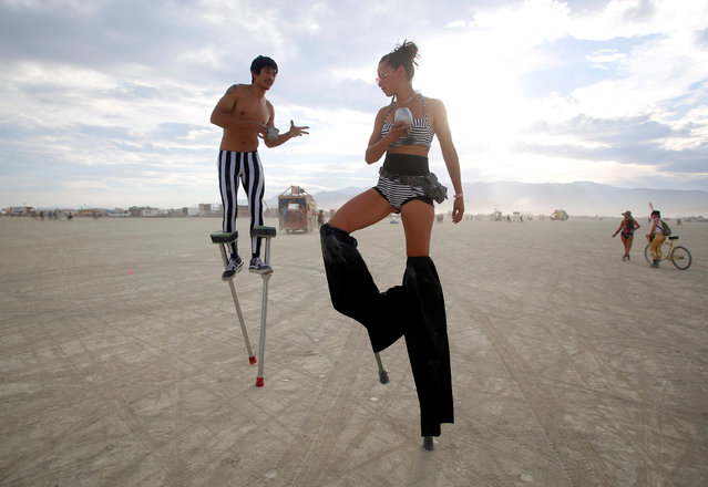 Divine Mustache (L) and Katapult Sandra, their Playa names, dance on stilts as approximately 70,000 people from all over the world gather for the 30th annual Burning Man arts and music festival in the Black Rock Desert of Nevada, U.S. August 29, 2016. (Photo by Jim Urquhart/Reuters)