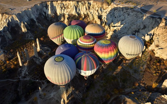 Hot air balloons glide in the sky during a trip over historical Cappadocia region, in Nevsehir, Turkey on October 28, 2017. (Photo by Murat Oner Tas/Anadolu Agency/Getty Images)