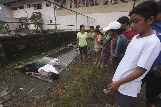 Residents look at bodies recovered from flashflood in New Bataan, Compostela Valley province, southern Philippines on Wednesday Dec. 5, 2012. The death toll from Typhoon Bhopa climbed to more than 100 people Wednesday, while scores of others remain missing in the worst-hit areas of the southern Philippines. (Photo by Karlos Manlupig/AP Photo)