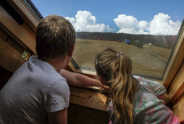 George Lee and sister Anna Lee watch from the sky light window of their home as an inter-island plane lands just behind their family's farm house on Sunday, February 14, 2016, in Port Howard, Falkland Islands. Port Howard is the main settlement on West Falkland Island.  During the week, the children attend school in Stanley, the country's capital on East Falkland Island. Their school transport options: either take a ferry and drive two hours or take a small plane that might make multiple island stops along the way. (Photo by Jahi Chikwendiu/The Washington Post)