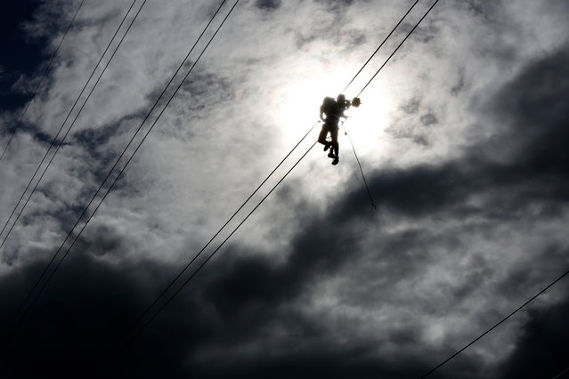 A technician works on an electricity transmission tower on the outskirts of Yangon, Myanmar on July 8, 2020. (Photo by Sai Aung Main/AFP Photo)