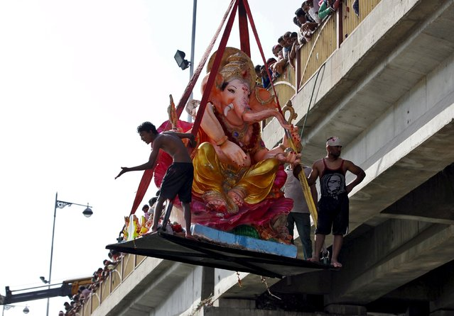 Devotees carry an idol of the Hindu god Ganesh, the deity of prosperity, as they use a crane for its immersion into the Sabarmati river on the last day of the 10-day-long Ganesh Chaturthi festival in Ahmedabad, India, September 27, 2015. (Photo by Amit Dave/Reuters)