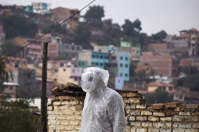 A state department health worker stands in full protective gear while recovering the body of a street vendor who was found at dawn by his neighbors in the Cerro San Miguel neighborhood of Cochabamba, Bolivia, Saturday, July 25, 2020. As part of a government mandated protocol to curb the spread of the new coronavirus, health officials are being called on to disinfect and take COVID-19 rapid tests from the increasing number of bodies they are called on to collect, regardless on whether they are known to have been infected with the virus. (Photo by Dico Solis/AP Photo)