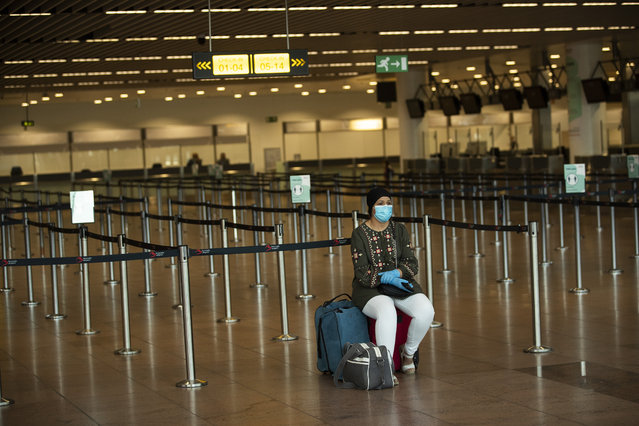A passenger, wearing a face mask to protect against the spread of coronavirus, sits at the almost empty departures hall at the Zaventem international airport in Brussels, Wednesday, July 29, 2020. Europe's tourism revival is running into turbulence only weeks after countries reopened their borders, with rising infections in Spain and other nations causing increasing concern among health authorities over people bringing the coronavirus home from their summer vacations. (Photo by Francisco Seco/AP Photo)