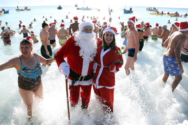 People dressed as Santa Claus take part in the traditional Christmas bath on December 17, 2017 in the French riviera city of Nice. (Photo by Valery Hache/AFP Photo)