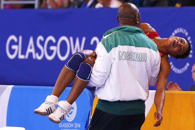Ifeoma Nwoye of Nigeria is carried away by her coach after she lost her women's freestyle 55kg wrestling semi-final to Brittanee Laverdure of Canada at the 2014 Commonwealth Games in Glasgow, Scotland, July 31, 2014. (Photo by Andrew Winning/Reuters)