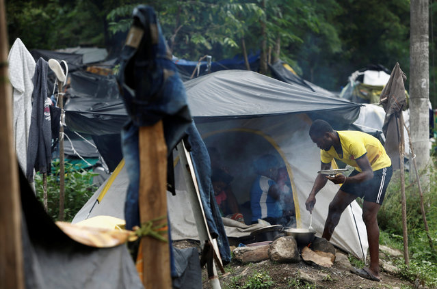 An African migrant stranded in Costa Rica cooks food in a makeshift camp at the border between Costa Rica and Nicaragua, in Penas Blancas, Costa Rica, September 7, 2016. (Photo by Juan Carlos Ulate/Reuters)