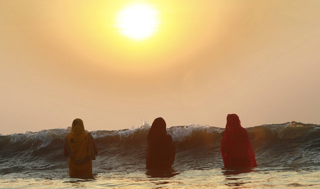 Hindu women offer prayers as the sun sets over the Arabian Sea during Chhath Puja festival in Mumbai, India, Wednesday, October 29, 2014. On Chhath, an ancient Hindu festival, rituals are performed to thank the Sun God for sustaining life on earth. (Photo by Rafiq Maqbool/AP Photo)