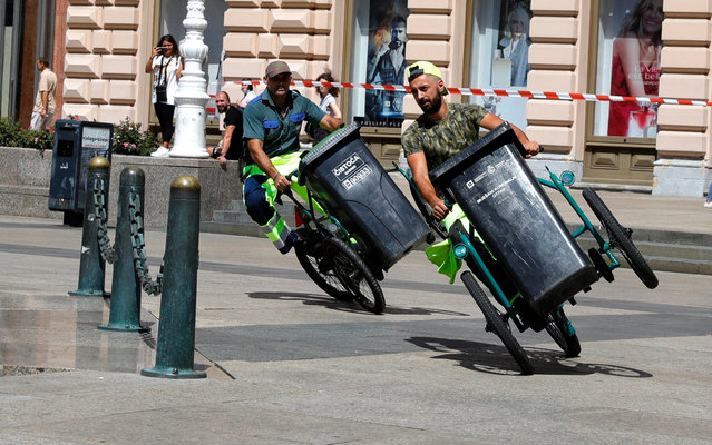 """Garbage men race on their tricycles along the track during the garbage men bicycle race at Ban Jelacic square in Zagreb, Croatia, 19 August 2020. Zagreb's authorities organised a street festival named """"Cest is the best"""" despite the coronavirus pandemic in Croatia with some 219 infected people. (Photo by Antonio Bat/EPA/EFE)"""