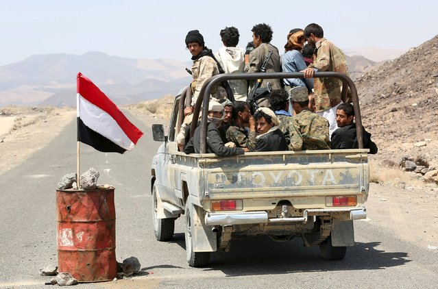 Tribal fighters loyal to Yemen's government ride a truck as they pass a barrel with a flag of Yemen sticking out from it at a check point on the frontline of fighting against Houthi militants in the central province of Marib October 8, 2015. (Photo by Reuters/Stringer)