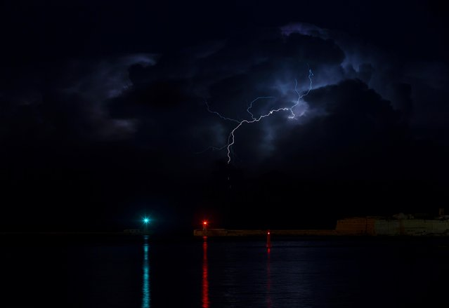 A lightning storm is seen beyond the entrance to Valletta's Grand Harbour, Malta on October 25, 2019. (Photo by Darrin Zammit Lupi/Reuters)