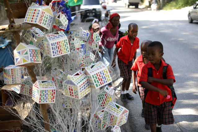 Kids look at Christmas decorations displayed for sale on a street of Port-au-Prince, Haiti, November 28, 2017. (Photo by Andres Martinez Casares/Reuters)
