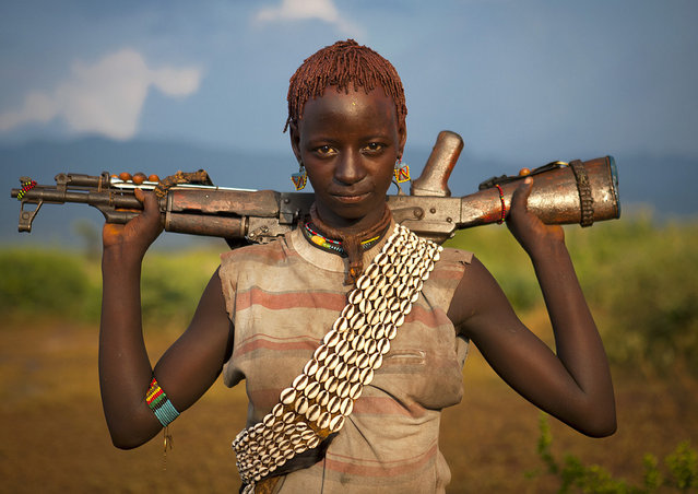 """Bana girl with gun – Omo valley Ethiopia. If you like girls with guns, go south Ethiopia! They are very nice to see! But when you know that they are totally drunk as it is part of a bull jumping ceremony, you feel a little bit unsafe!"". (Photo and comment by Eric Lafforgue)"