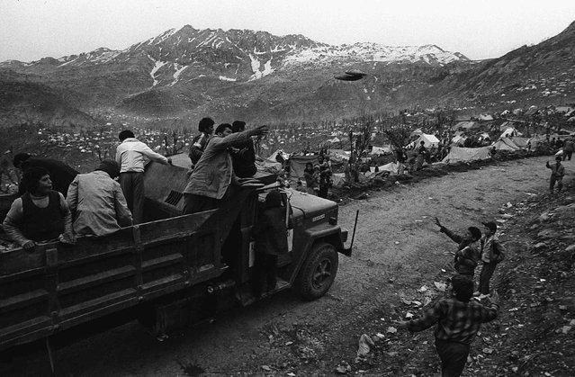 Men throw bread from a truck to Iraqi Kurdish refugees in Cukurca refugee camp in Turkey April 9, 1991. (Photo by Srdjan Zivulovic/Reuters)